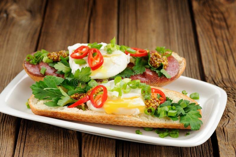 Sandwichs à oeufs pochés avec le piment, l'oignon blanc et le salami photographie stock libre de droits