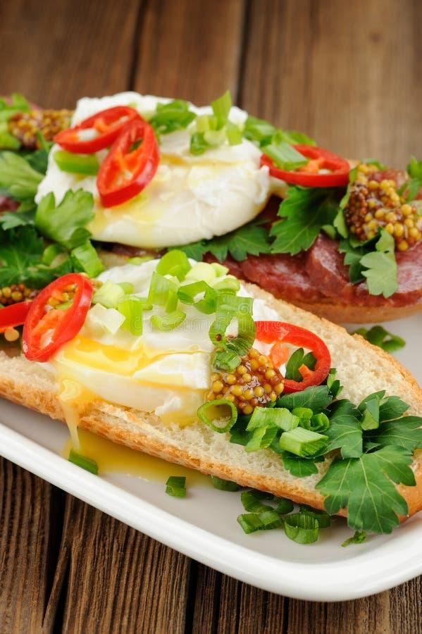 Sandwichs à oeufs pochés avec le piment, l'oignon blanc et le salami photographie stock