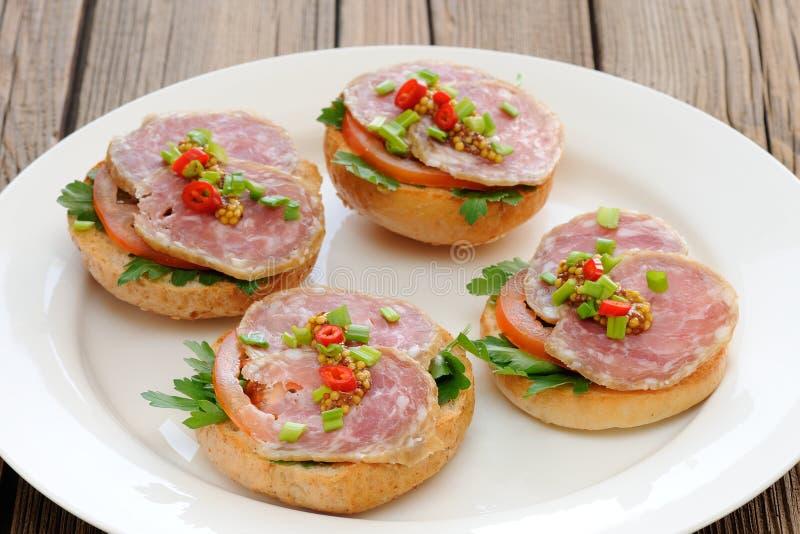 Sandwichs au jambon avec le piment, le persil et l'oignon blanc du plat blanc photos stock
