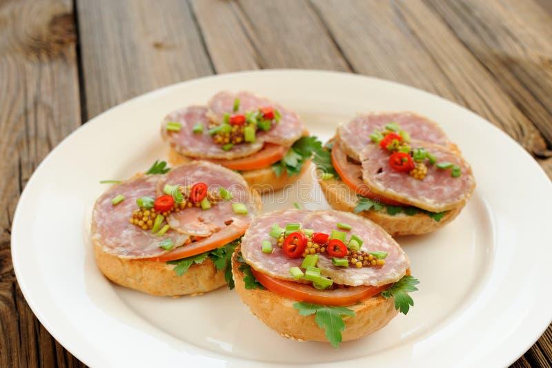 Sandwichs au jambon avec le piment, le persil et l'oignon blanc du plat blanc image libre de droits