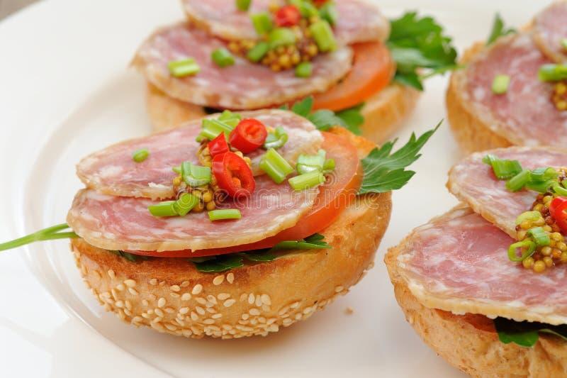 Sandwichs au jambon avec le piment, le persil et l'oignon blanc du plat blanc c images stock