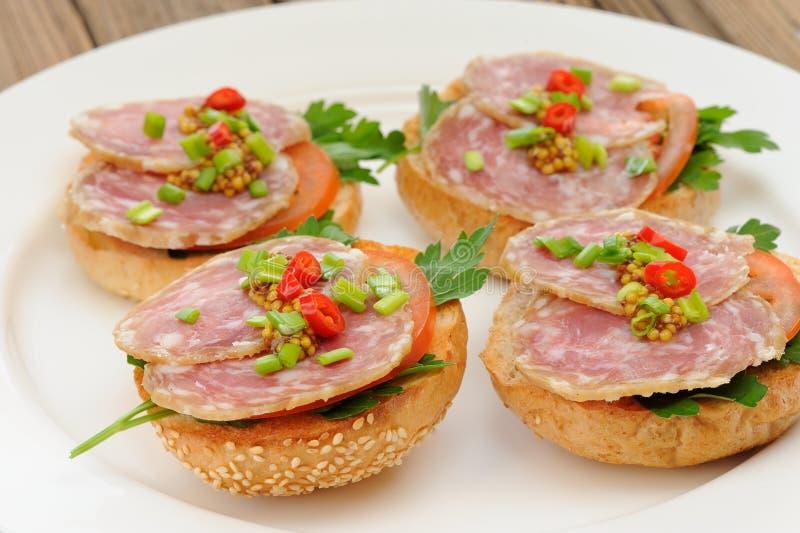 Sandwichs au jambon avec le piment, le persil et l'oignon blanc du plat blanc c image libre de droits