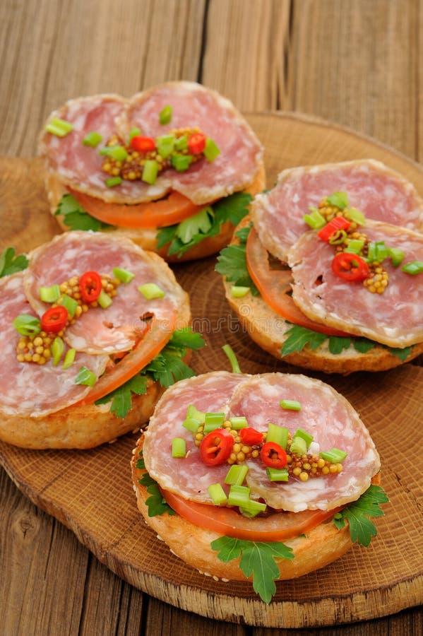 Sandwichs au jambon avec le piment, le persil et l'oignon blanc sur le conseil en bois photographie stock