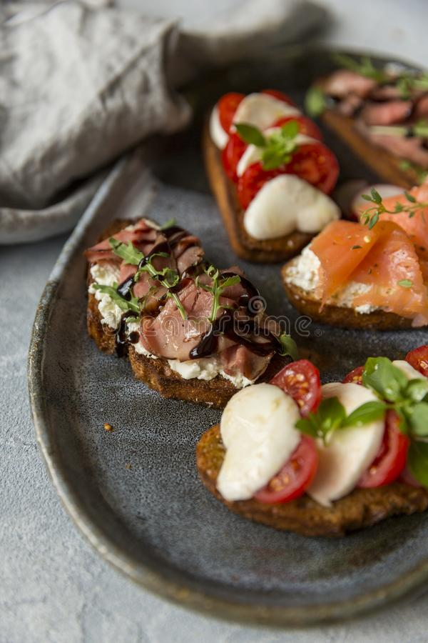 Sandwichs avec du boeuf et arugula de rôti, saumons et cumin, mozzarella et tomates sur le pain brun images stock