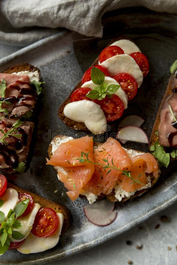 Sandwichs avec du boeuf et arugula de rôti, saumons et cumin, mozzarella et tomates sur le pain brun image stock