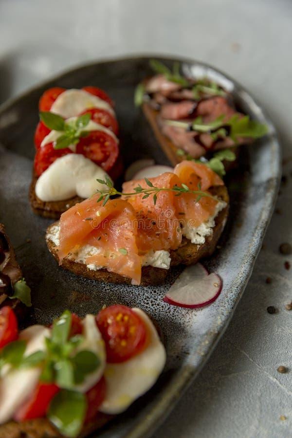 Sandwichs avec du boeuf et arugula de rôti, saumons et cumin, mozzarella et tomates sur le pain brun photo libre de droits