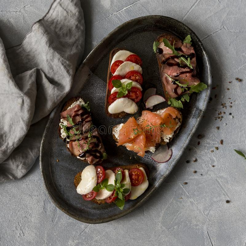Sandwichs avec du boeuf et arugula de rôti, saumons et cumin, mozzarella et tomates sur le pain brun photos libres de droits