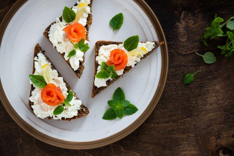 Sandwichs avec du pain de c?r?ales, le fromage saumon? et frais, le basilic et le citron du plat Vue sup?rieure, l'espace de copi photo libre de droits