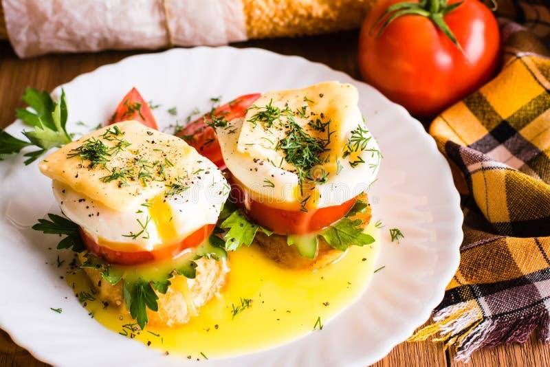Sandwichs avec l'oeuf poché, la tomate, le persil et le fromage photos libres de droits