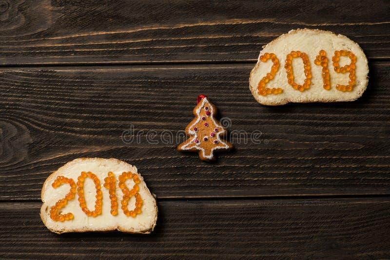 Sandwichs avec le caviar 2018 et 2019 rouge sur différentes lignes avec le petit pin de jouet entre image libre de droits
