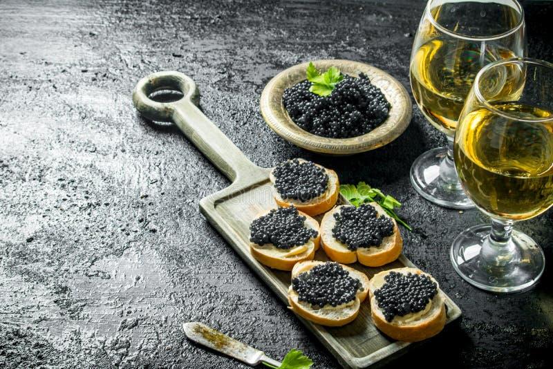 Sandwichs avec le caviar noir et le vin photographie stock