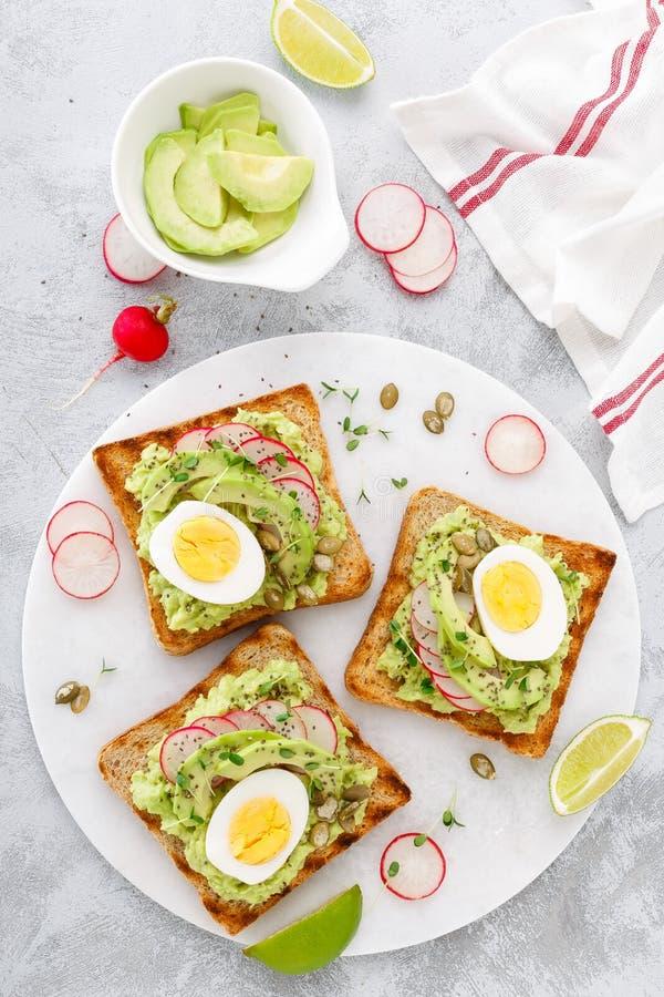 Sandwichs avec le guacamole d'avocat, les graines fraîches de radis, d'oeuf à la coque, de chia et de citrouille Usine-b délicieu image stock