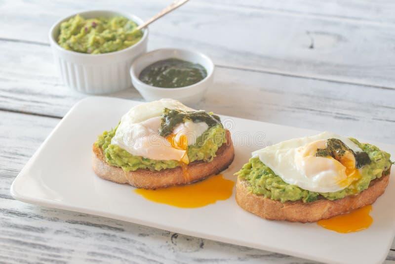 Sandwichs avec le guacamole et les oeufs pochés photographie stock