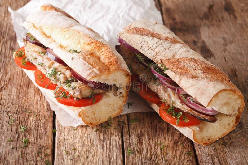 Sandwichs avec le maquereau, les tomates frites et les oignons en gros plan Ho image libre de droits