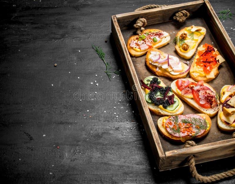 Sandwichs avec les fruits de mer, la viande et les légumes sur le pain frais photo stock
