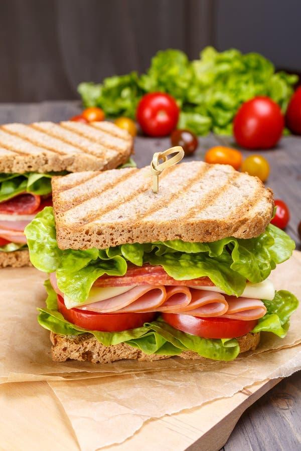 Sandwichs délicieux à jambon, à salami, à fromage et à légumes sur le pain entier de grain Toasted d'isolement sur le blanc photos stock