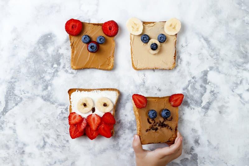 Sandwichs drôles sains à visage pour des enfants L'animal fait face au pain grillé avec du beurre d'arachide et d'anarcadier, ric photos libres de droits