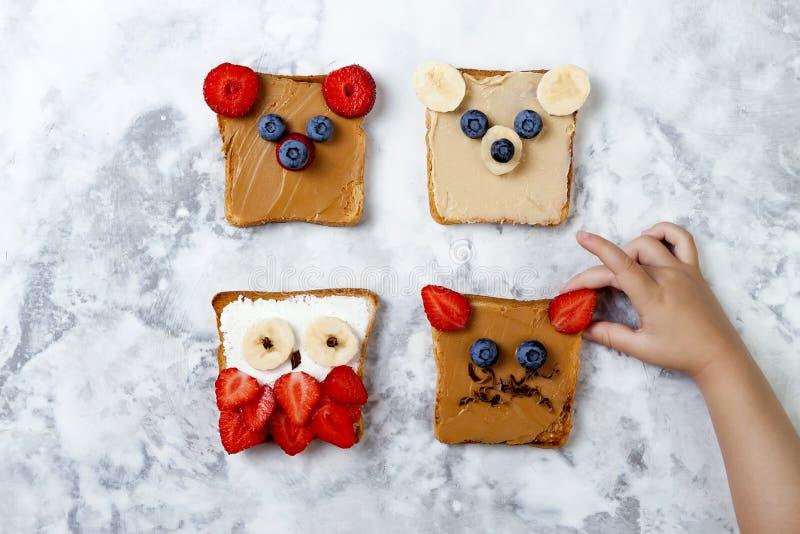 Sandwichs drôles sains à visage pour des enfants L'animal fait face au pain grillé avec du beurre d'arachide et d'anarcadier, ric images stock