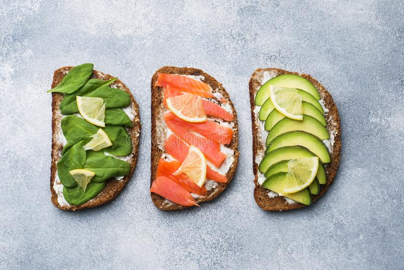 Sandwichs ouverts avec des saumons d'épinards et d'avocat sur une table grise photo libre de droits