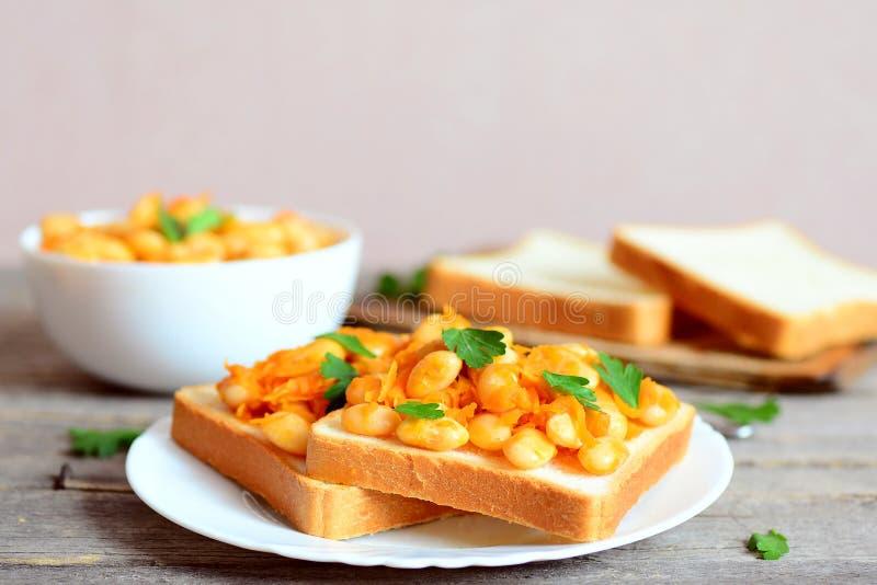 Sandwichs ouverts faits maison avec les haricots blancs cuits au four Les haricots ont fait cuire au four avec la sauce de carott photographie stock