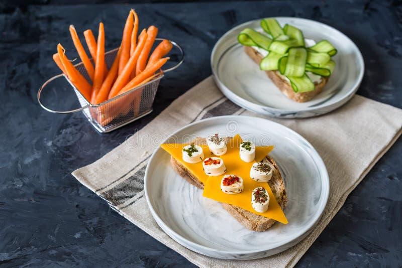 Sandwichs ouverts sains avec des légumes, des carottes, le fromage de cheddar et le concombre sur un fond en bois photo libre de droits