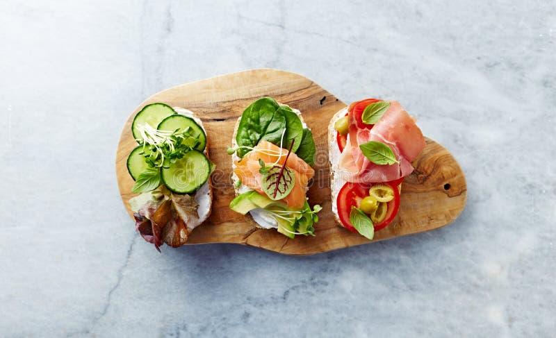 Sandwichs ouverts sains avec des légumes, des herbes, des saumons, le jambon, des herbes et le fromage à pâte molle Concept de ré photographie stock