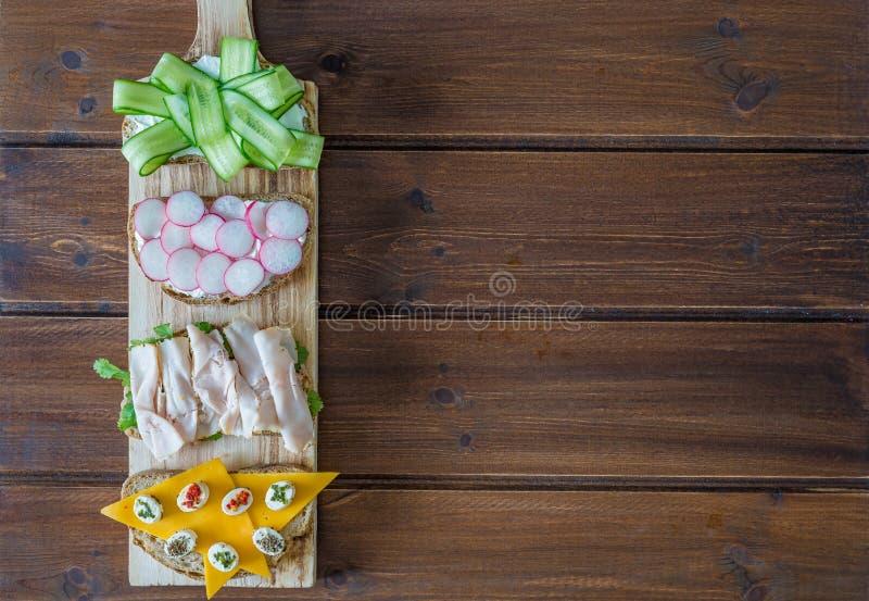 Sandwichs ouverts sains avec les légumes, le fromage de cheddar de pastrami de dinde de radis de concombre et le fromage à pâte m images stock