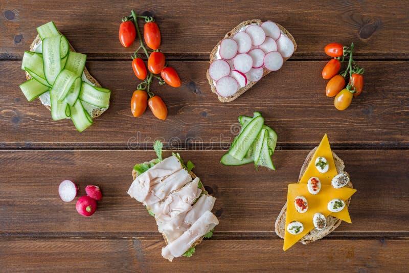 Sandwichs ouverts sains avec les l?gumes, le fromage de cheddar de pastrami de dinde de radis de concombre et le fromage ? p?te m photographie stock