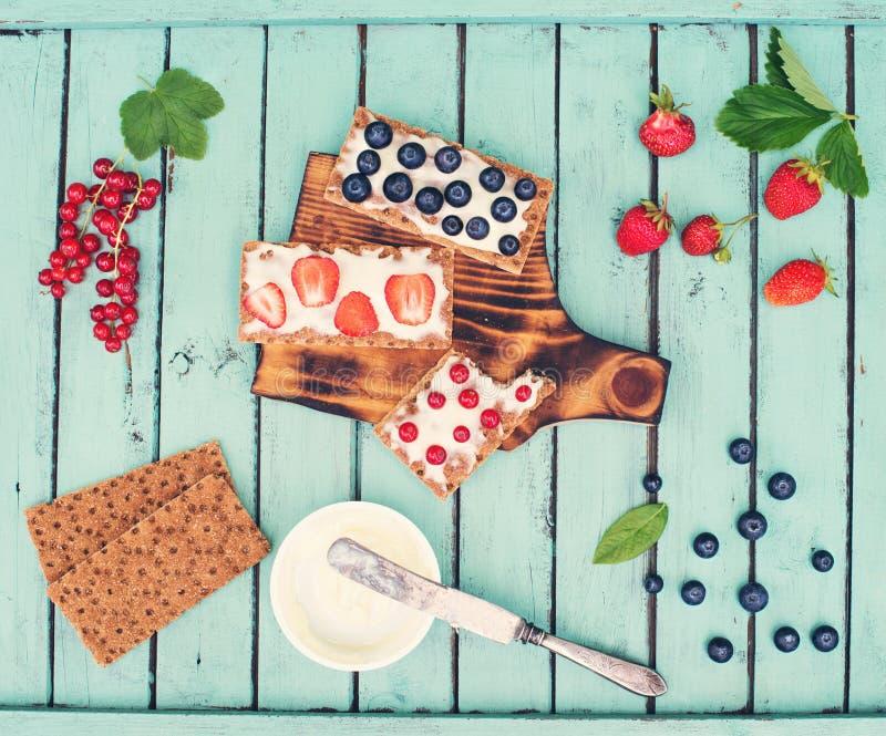 Sandwichs sains avec le fromage à pâte molle et les baies sur des chips de pain sur le fond chic minable Concept sain de cadeaux  photos stock