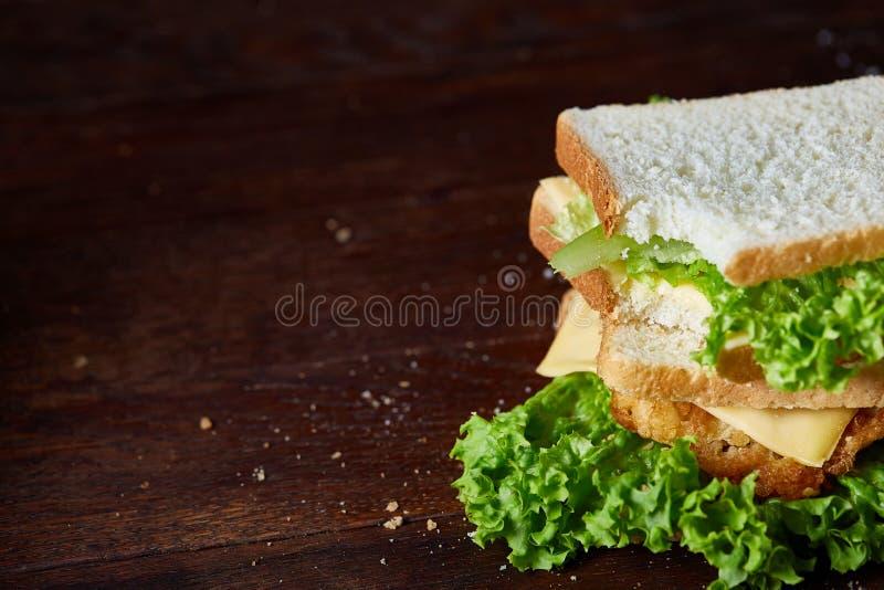 Sandwichs savoureux et frais sur la planche à découper au-dessus d'un fond en bois foncé, plan rapproché images libres de droits