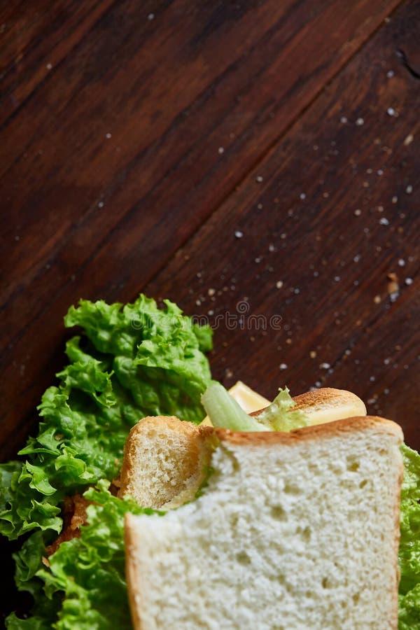 Sandwichs savoureux et frais sur la planche à découper au-dessus d'un fond en bois foncé, plan rapproché image libre de droits