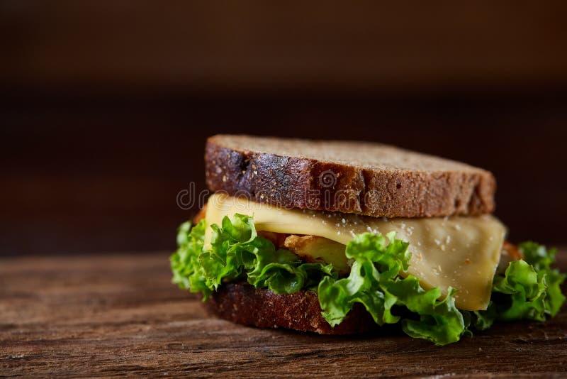 Sandwichs savoureux et frais sur la planche à découper au-dessus d'un fond en bois foncé, plan rapproché photo libre de droits