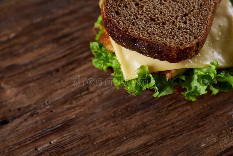 Sandwichs savoureux et frais sur la planche à découper au-dessus d'un fond en bois foncé, plan rapproché photos libres de droits