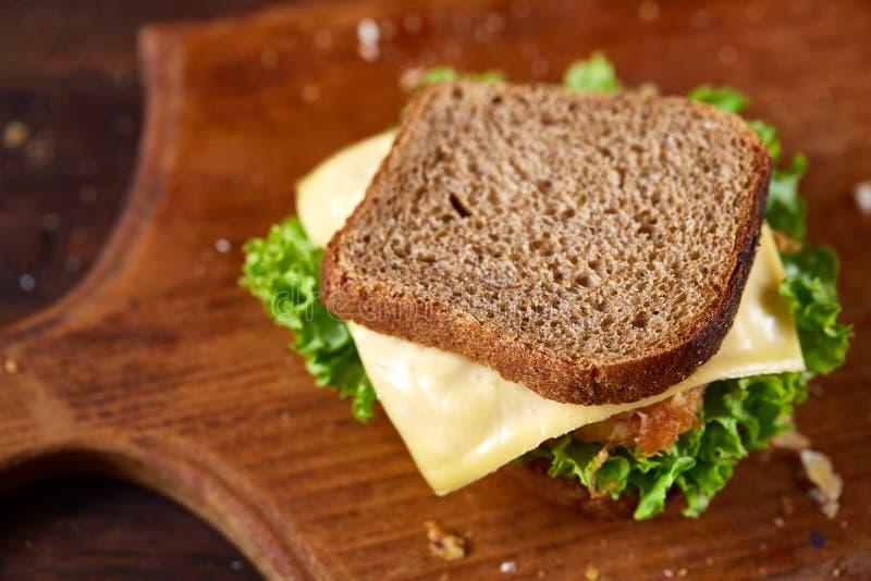 Sandwichs savoureux et frais sur la planche à découper au-dessus d'un fond en bois foncé, plan rapproché images stock