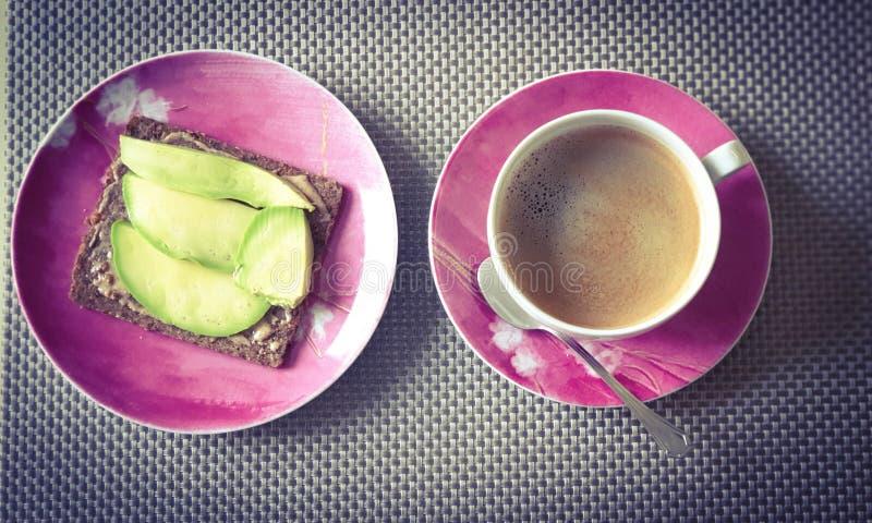 Sandwiich чашки кофе и авокадоа на красных плитах стоковые фотографии rf