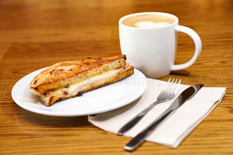 Sandwish e caffè sulla tavola di legno di mattina fotografie stock libere da diritti