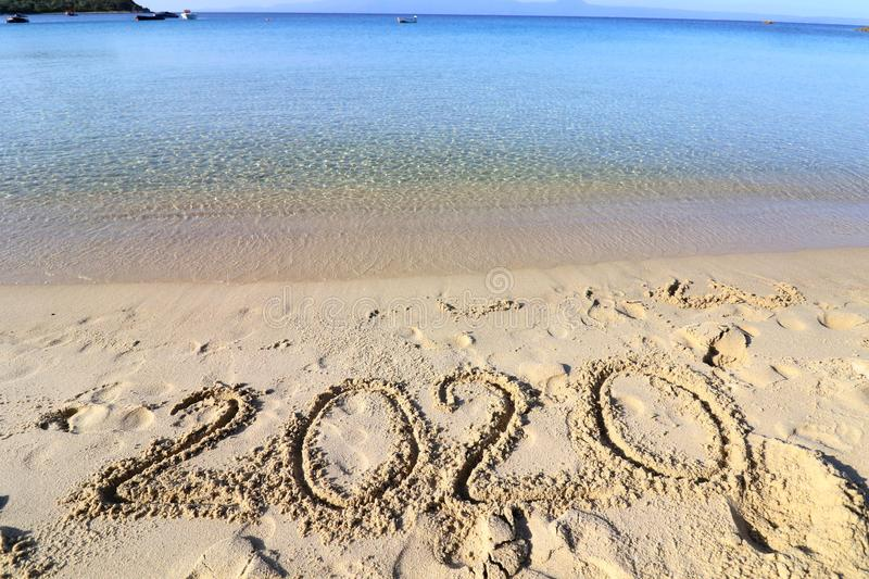 2020 on a sandy background on the beach. New Years concept. stock photos
