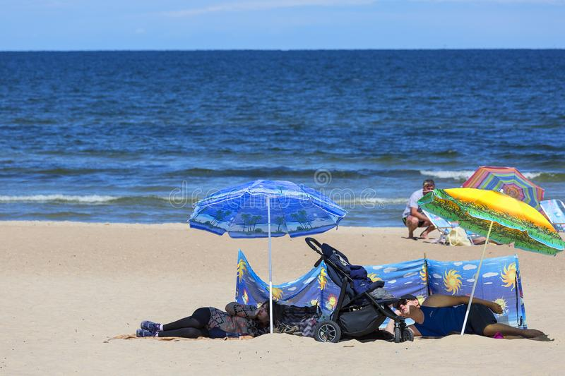 Sandy beach on the Baltic sea, people resting on a sunny summer day, sunshade, Sopot, Poland royalty free stock photo