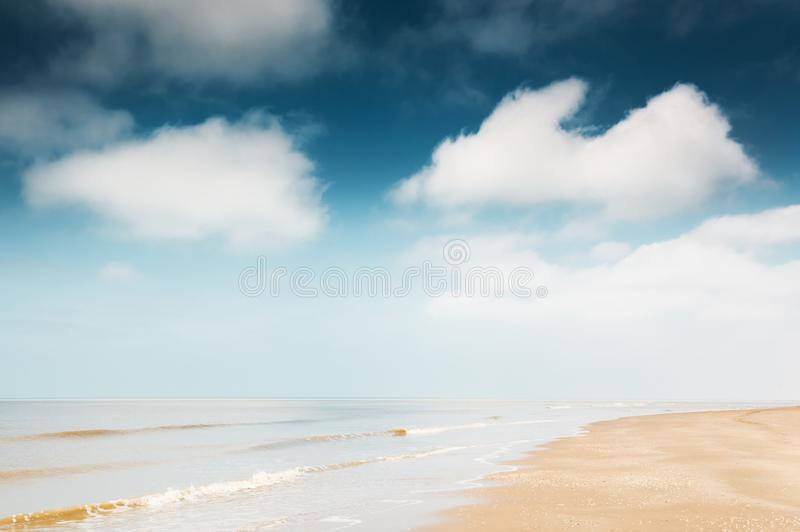 Sandy beach and blue sky with clouds. stock photography