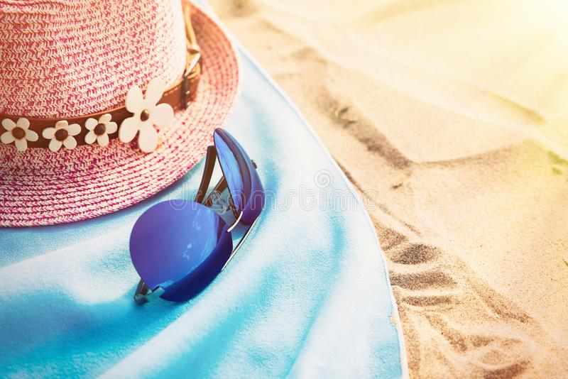 Sandy beach with a blue towel with a hat and glasses. copy space and visible sand texture. Selective focus. stock images