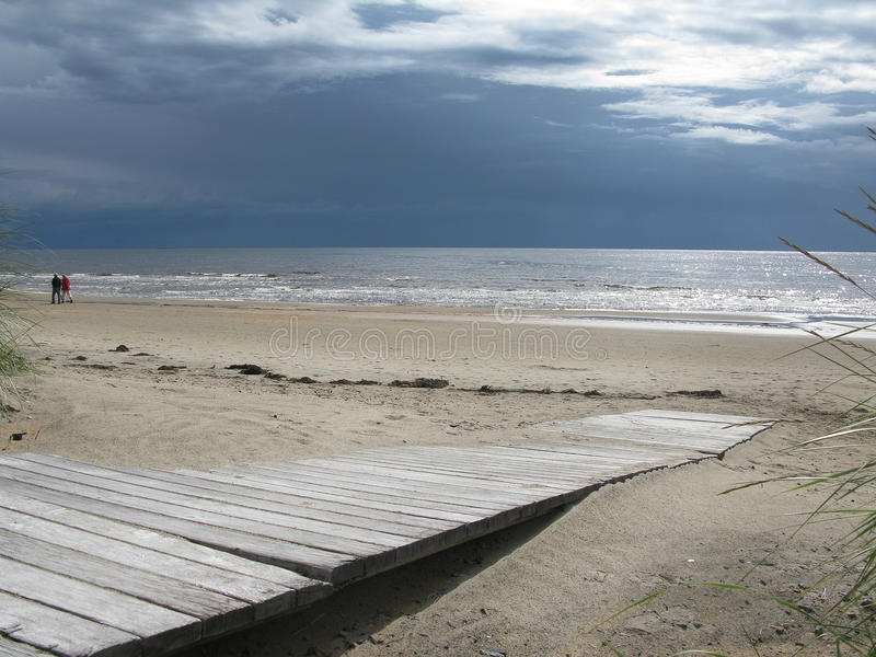 Sandy beach boardwalk. Sand dune landscape with wooden boardwalk leading towards sea and sky at Skrea Strand on a sunny day with dark clouds in Falkenberg royalty free stock image