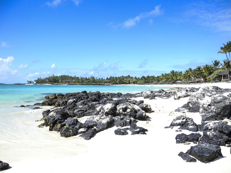 Sandy Beach branco com dispersão das rochas no mar do pelotão da frente e do aqua com cacho da palma na distância fotos de stock