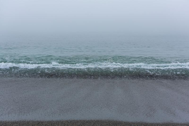 Sandy beach with the calm sea. On a foggy day stock photos