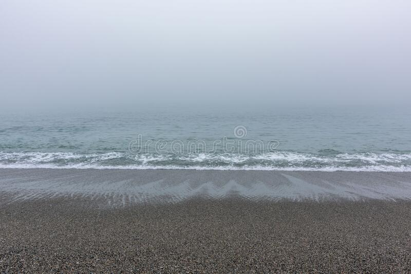 Sandy beach with the calm sea. On a foggy day royalty free stock photo