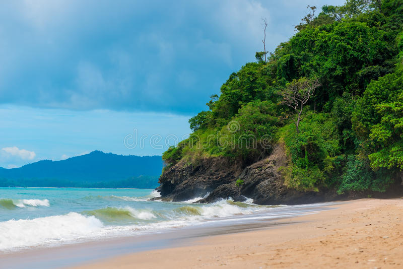 Sandy beach and cliffs of Thailand in inclement weather. Dark blue sky over the sea stock photo