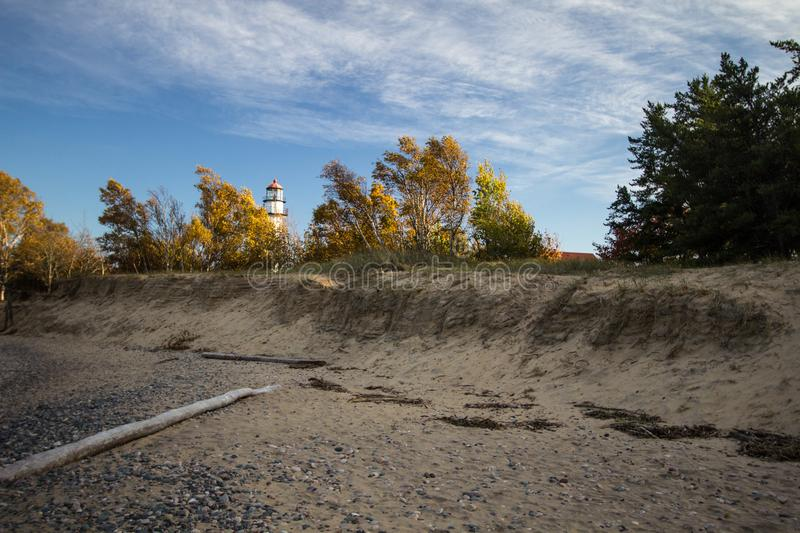 Michigan Autumn Lighthouse Beach Background. Sandy beach on the coast of Lake Superior with the Whitefish Point Lighthouse in the background framed by autumn stock images