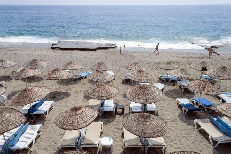 Sandy Beach com vadios do sol e guarda-chuvas da palha na costa de mar turca, mar Mediterrâneo fotos de stock royalty free