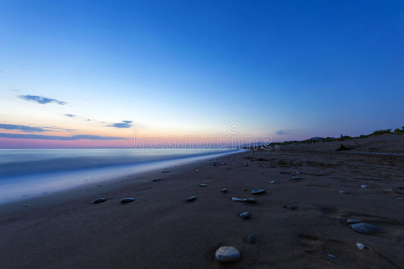 Sandy beach at the dusk, Peloponnese - Greece. View of a beautiful sandy beach at the dusk. Coastline of Kyparissia, Peloponnese - Greece. Long exposure shot royalty free stock images
