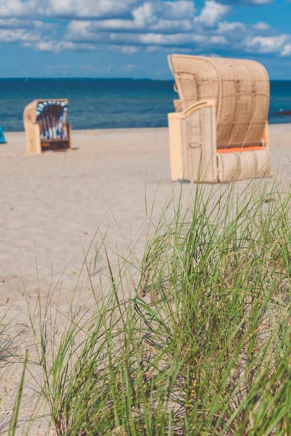 Sandy Beach e cadeiras de praia de madeira tradicionais Alemanha do norte, na costa do mar Báltico imagens de stock royalty free