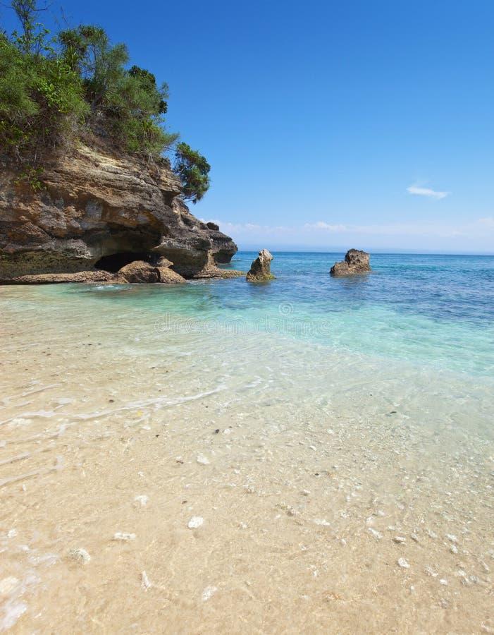 Sandy Beach em rochas no oceano. Indonésia, imagens de stock